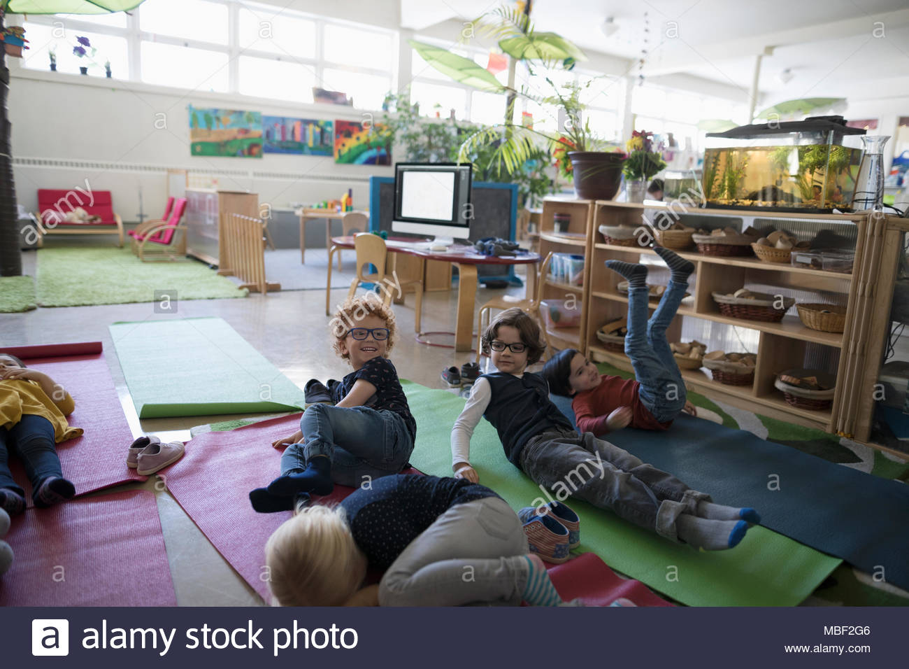 Tired preschool students resting on yoga mats during nap time - Stock Image