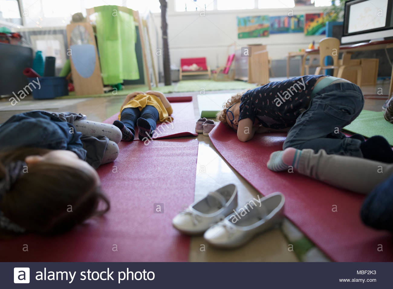 Tired preschool students sleeping on yoga mats during nap time - Stock Image