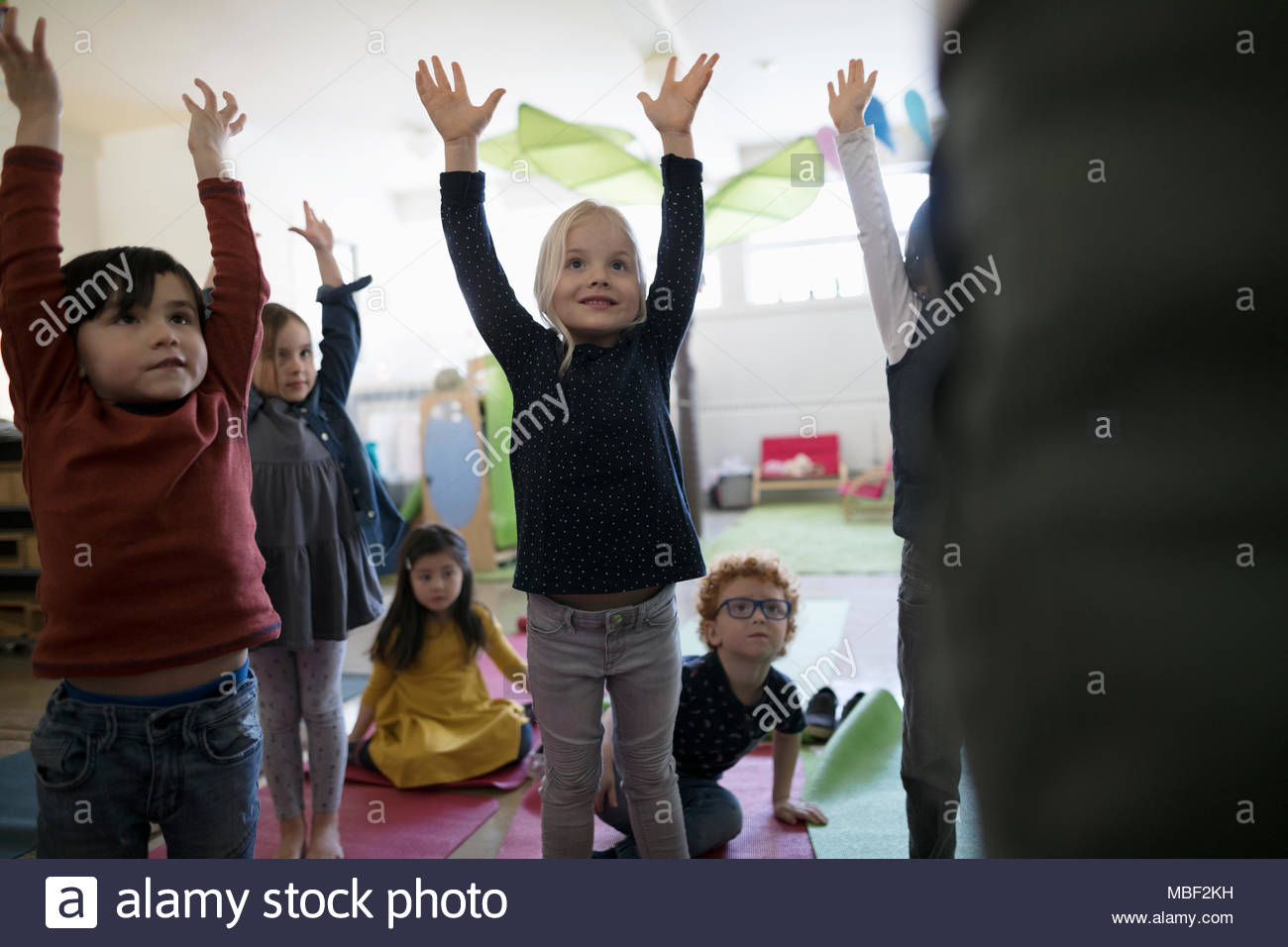 Preschool students practicing yoga with arms raised in classroom - Stock Image