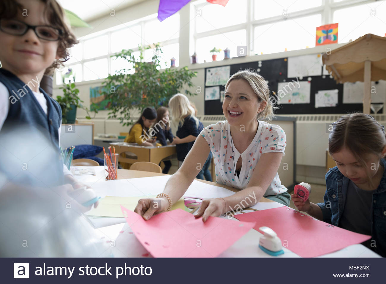 Preschool teacher and students making art and craft projects in classroom - Stock Image
