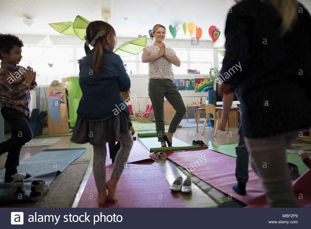 Preschool teacher and students practicing yoga tree pose in classroom - Stock Image