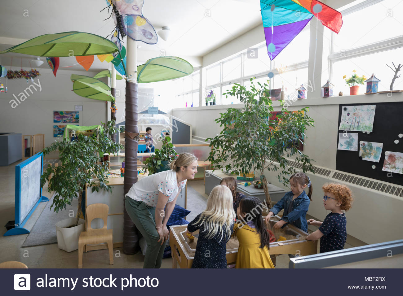 Preschool teacher and students playing at sandbox - Stock Image
