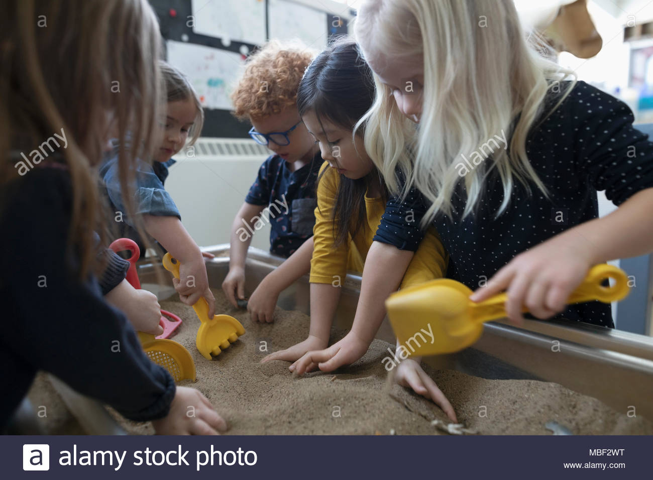Preschool students playing in sandbox - Stock Image