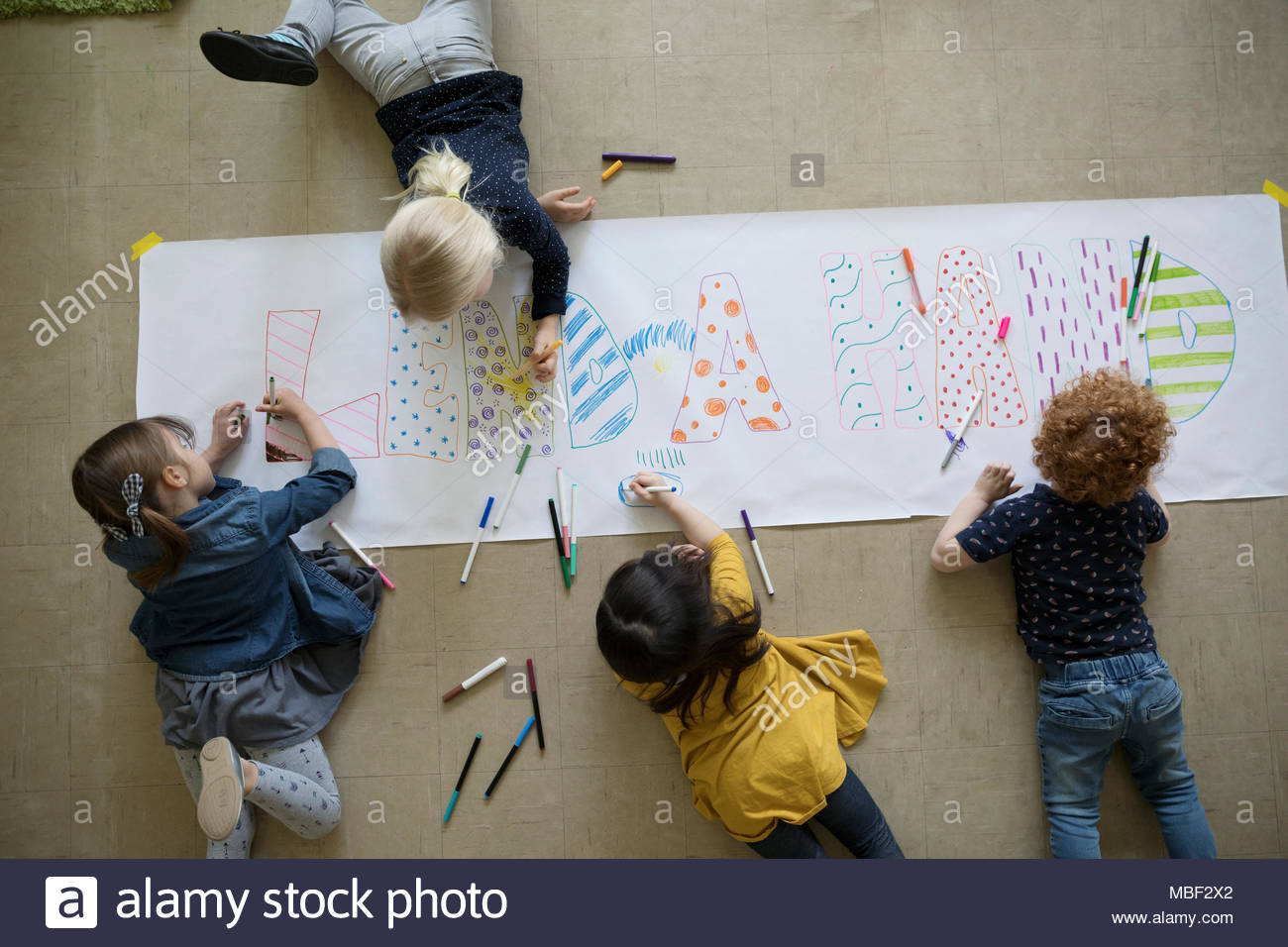 Community focused preschool students with markers drawing on poster - Stock Image