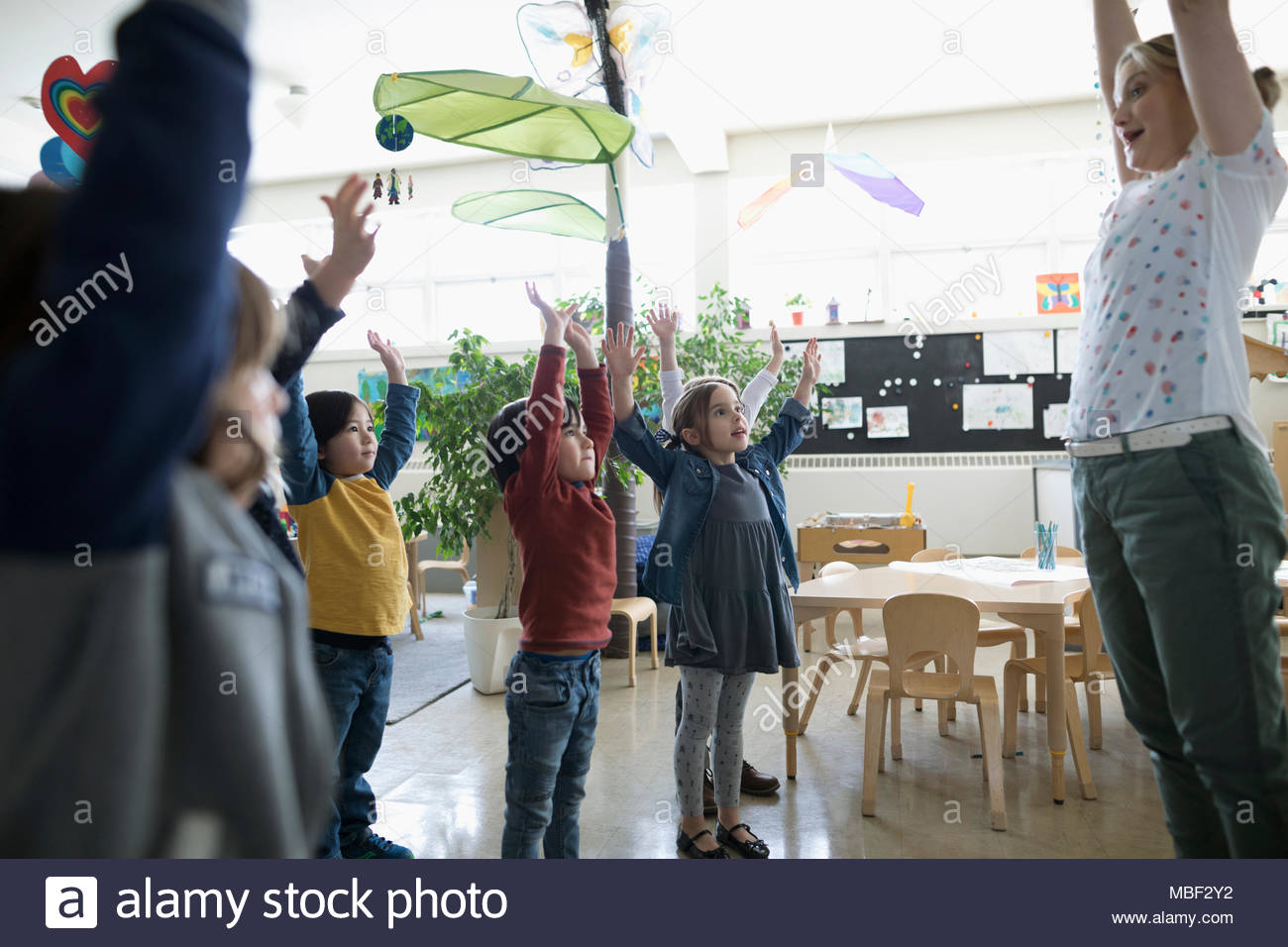 Preschool teacher and students exercising with arms raised in classroom - Stock Image