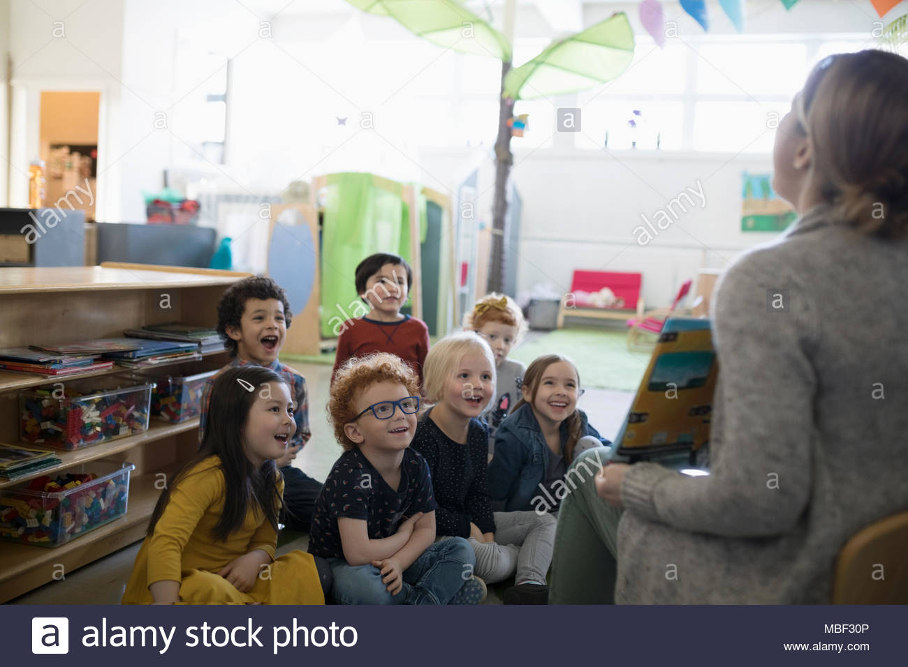 Preschool students listening to teacher reading book during story time in classroom - Stock Image