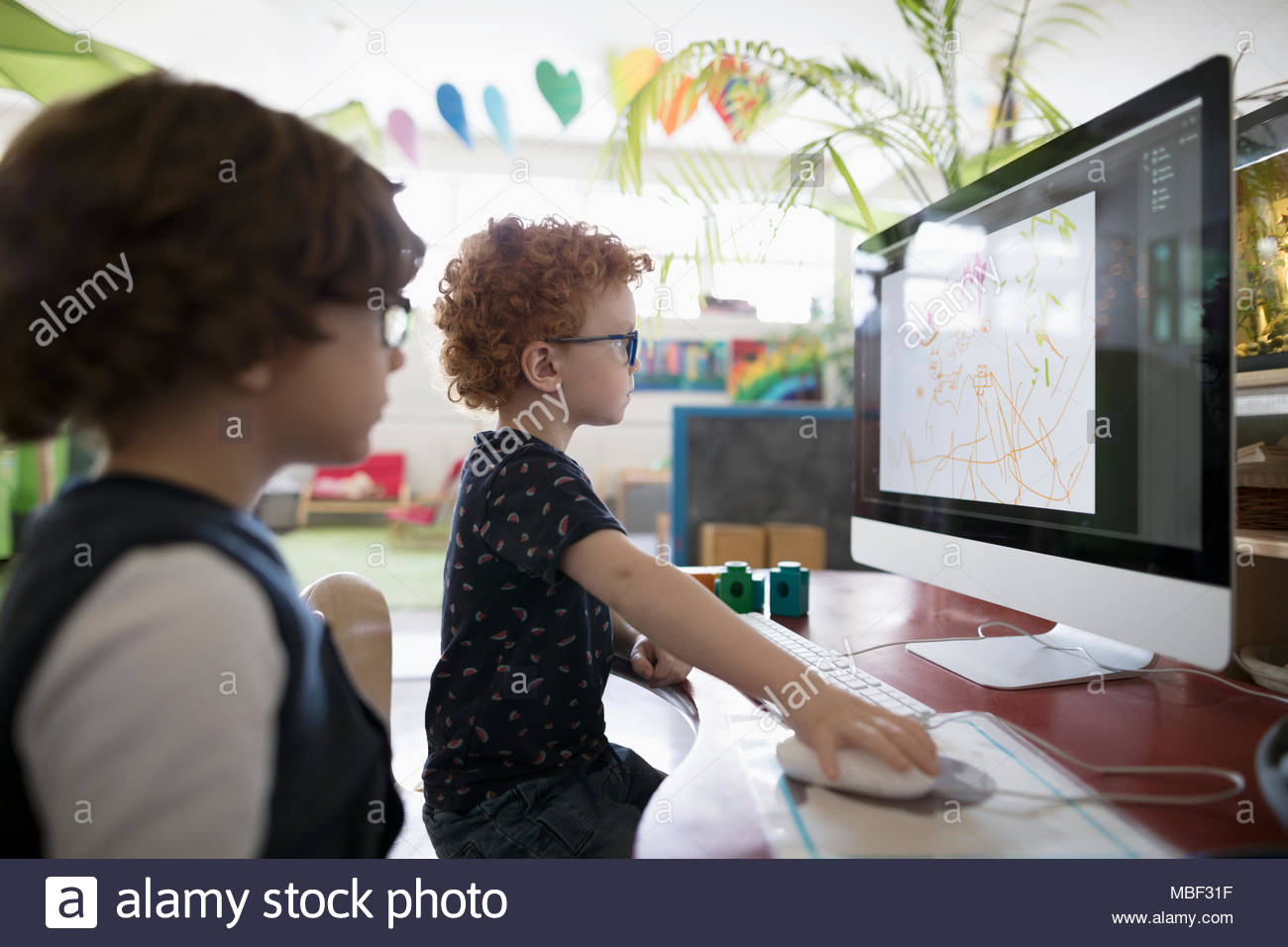 Preschool boy students drawing at computer in classroom - Stock Image