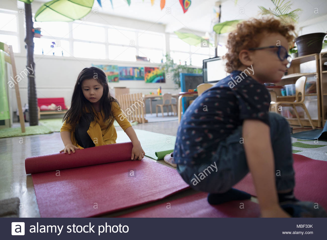 Preschool students rolling up yoga mats in classroom - Stock Image