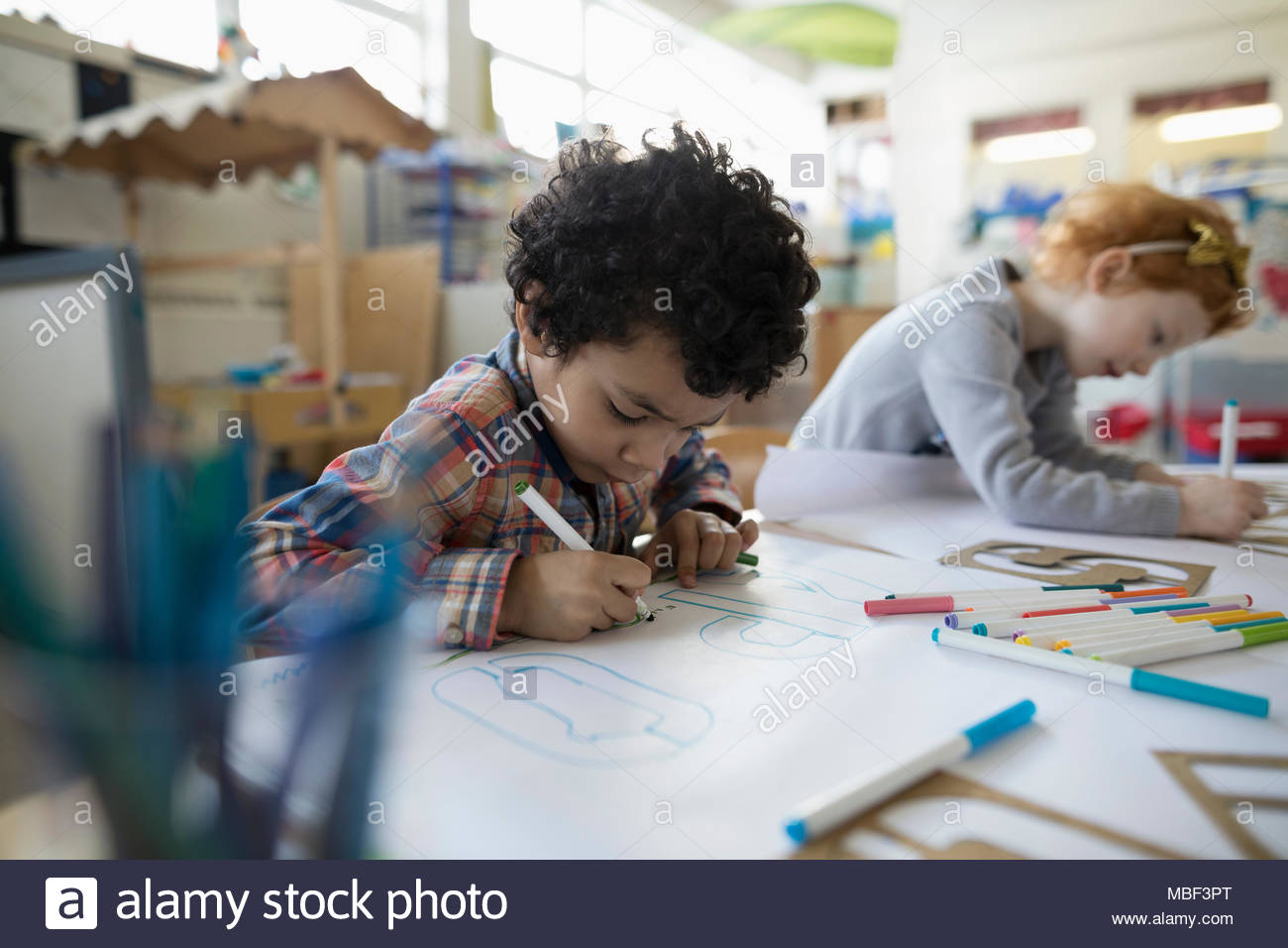 Focused preschool boy drawing letters with marker in classroom - Stock Image