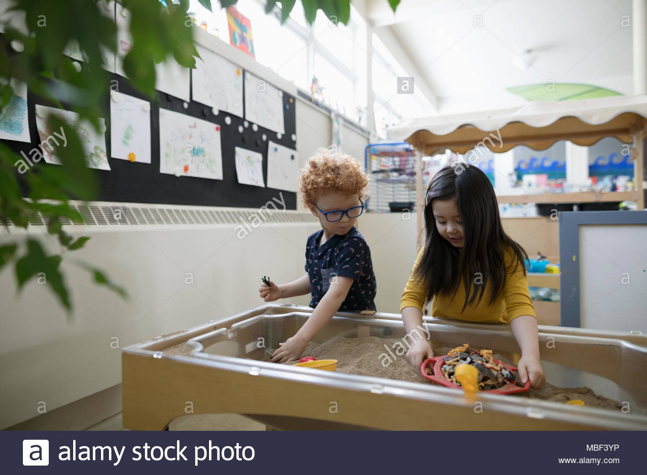 Preschool boy and girl playing in sandbox in classroom - Stock Image