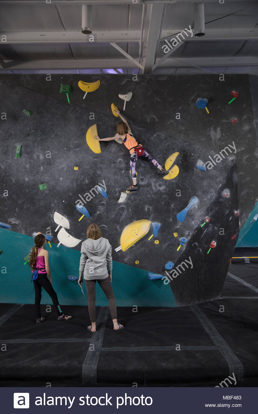 Female rock climbing instructor and girl watching rock climber climbing wall in climbing gym - Stock Image