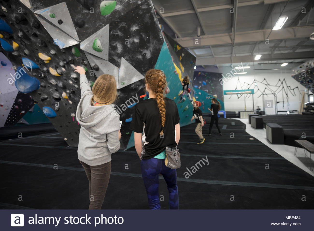 Female instructor guiding girl rock climbing student at climbing wall in climbing gym - Stock Image