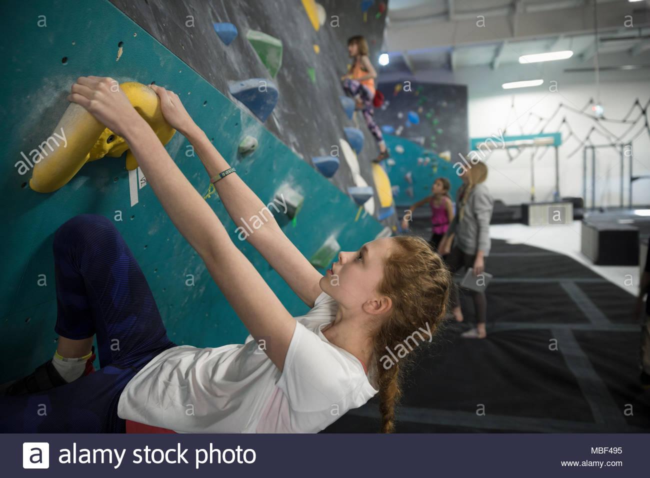 Focused, strong girl rock climber climbing wall in climbing gym - Stock Image