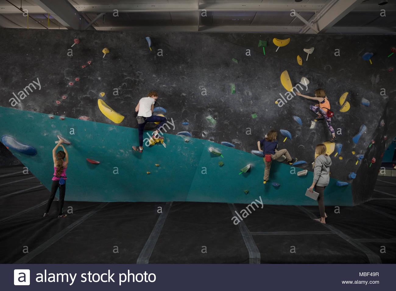 Girl rock climbing students climbing wall at climbing gym - Stock Image