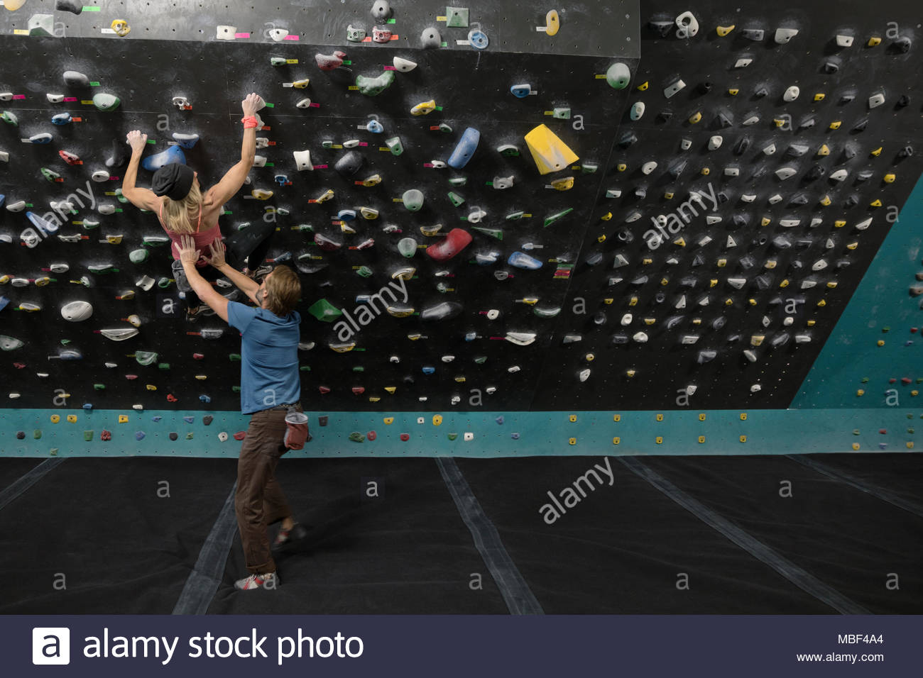 Male rock climber spotting, supporting female rock climber climbing wall at climbing gym - Stock Image