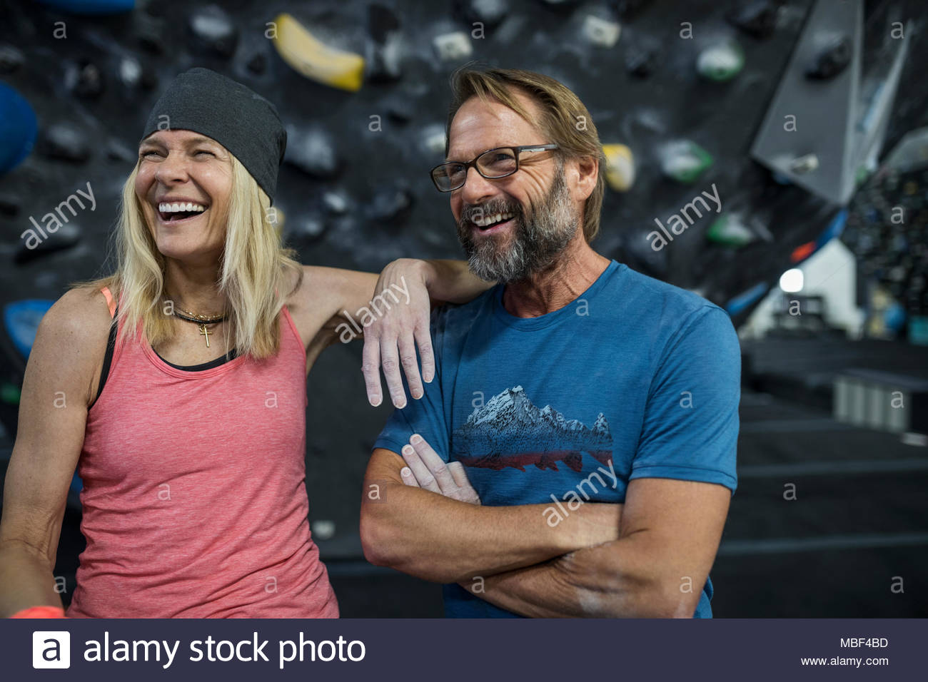Happy mature couple rock climbers laughing at climbing gym - Stock Image