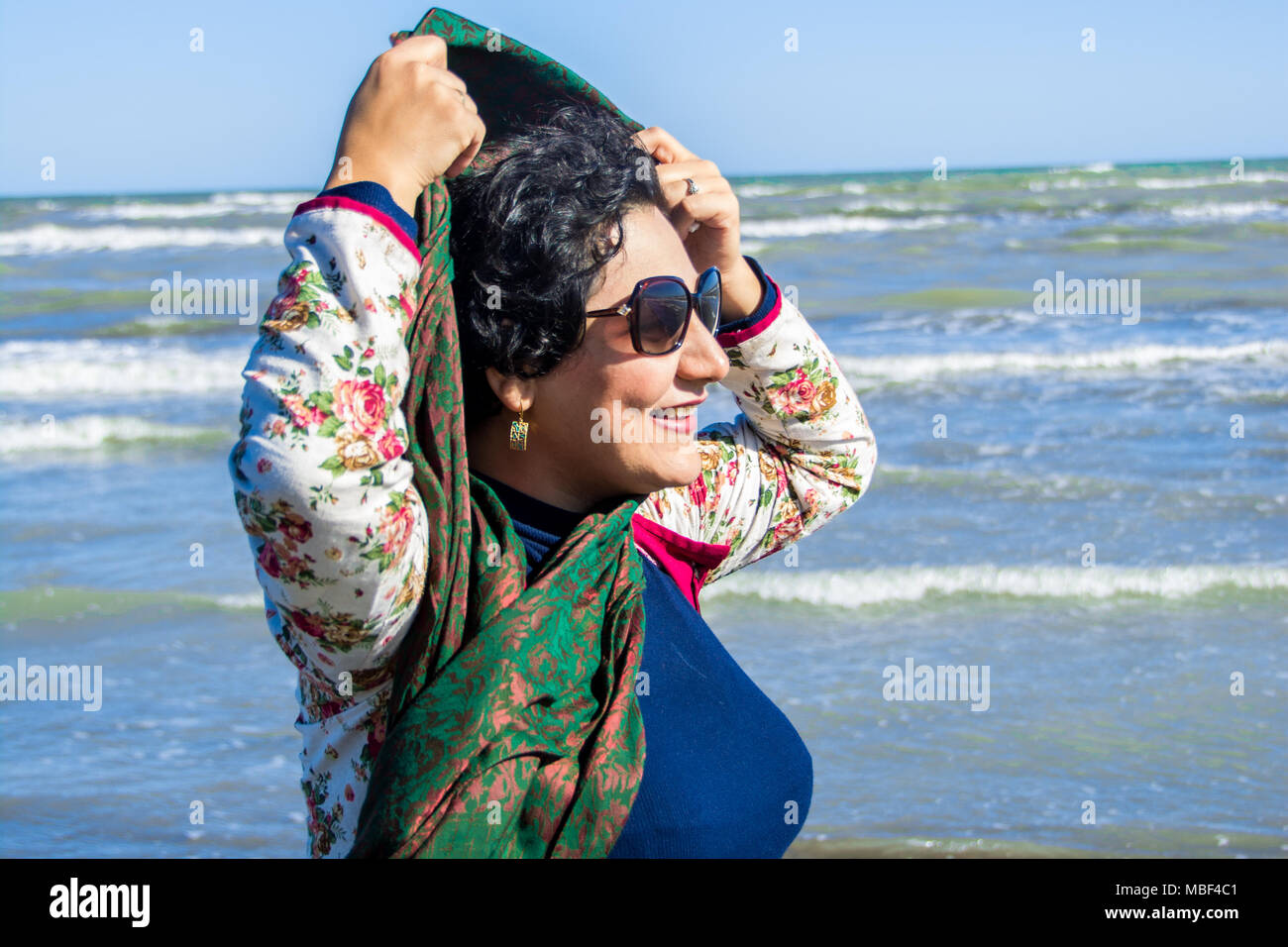 happy Iranian woman with easy hijab in beach of Caspian sea - Stock Image