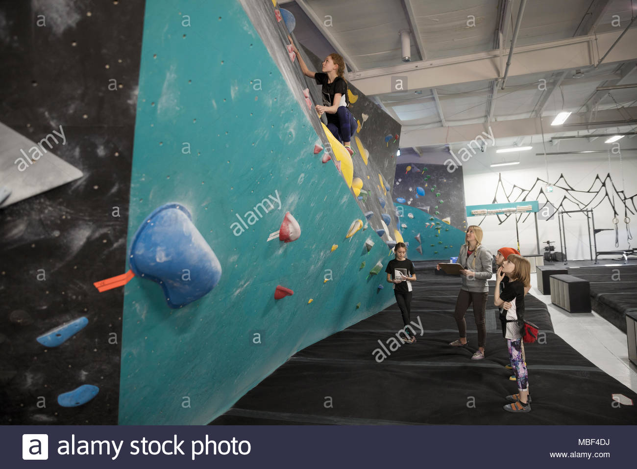 Female instructor and rock climbing students watching girl climbing wall at climbing gym - Stock Image