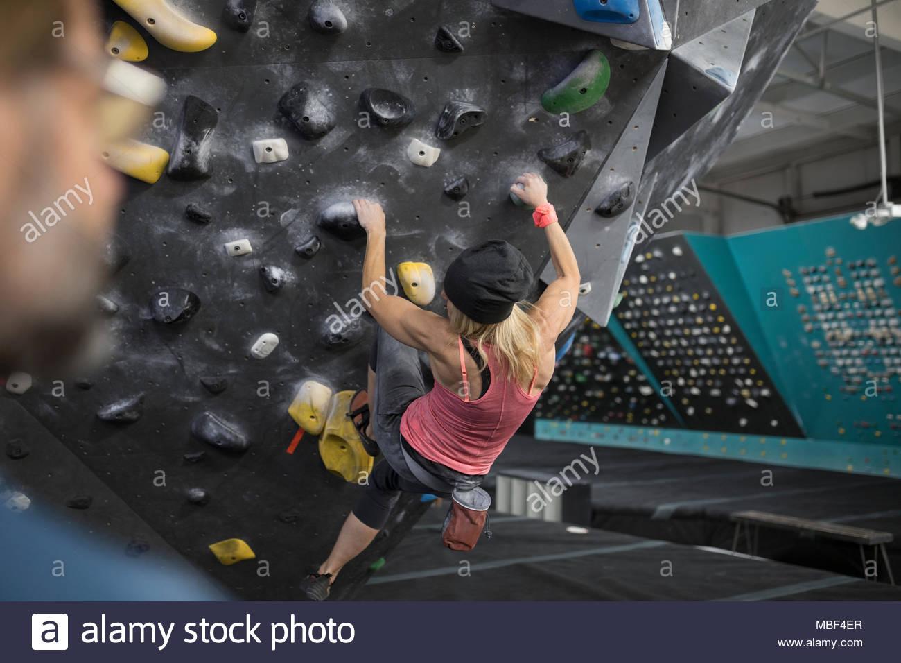 Strong, tough mature female rock climber climbing wall at climbing gym - Stock Image
