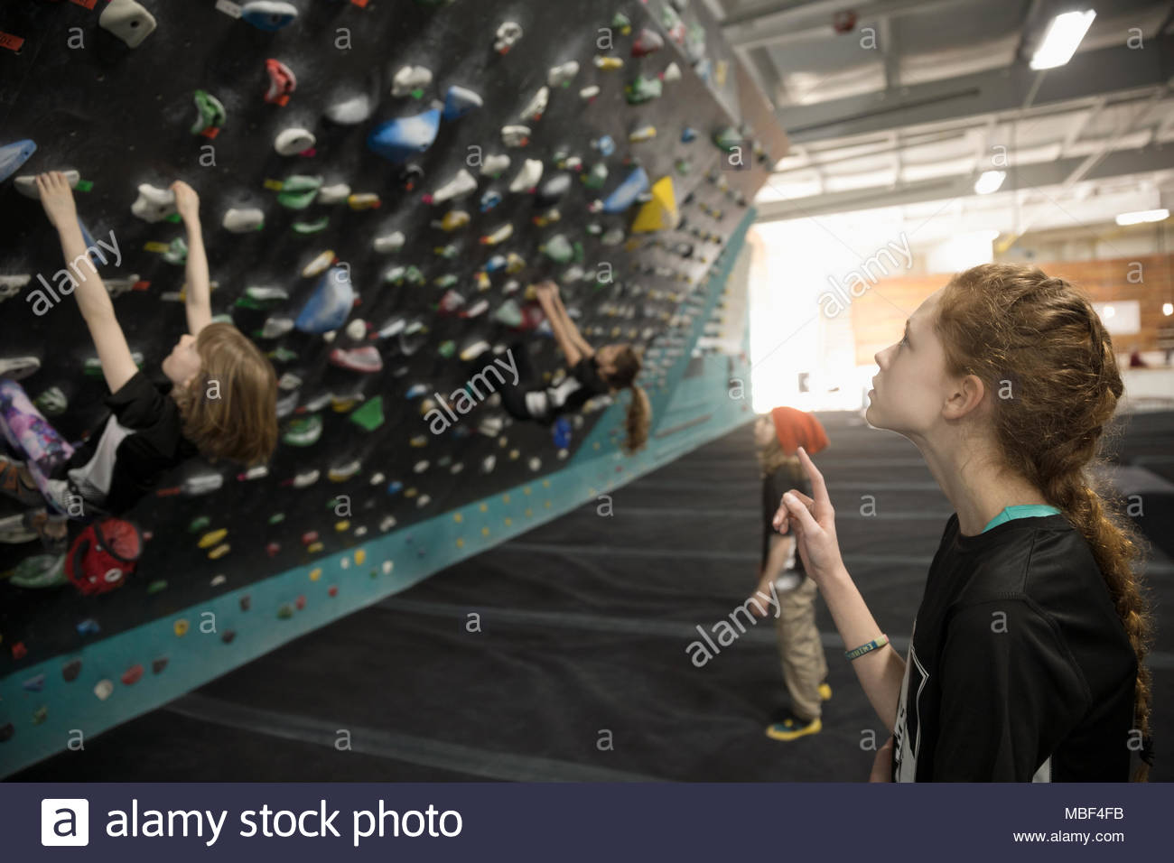 Curious girl rock climber watching friend climbing wall in climbing gym - Stock Image