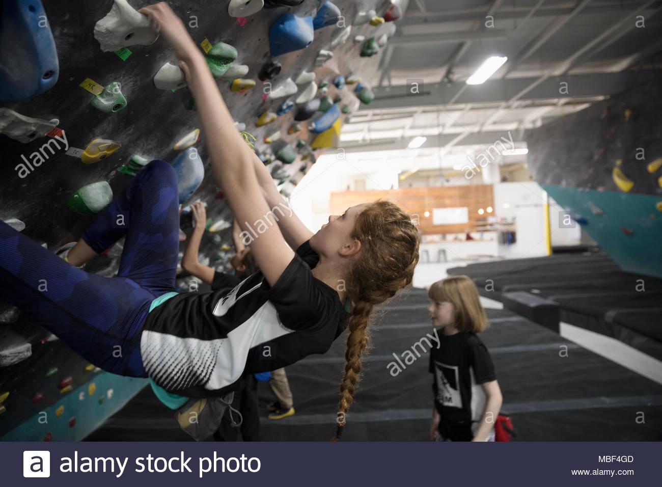 Girl rock climber climbing wall at climbing gym - Stock Image