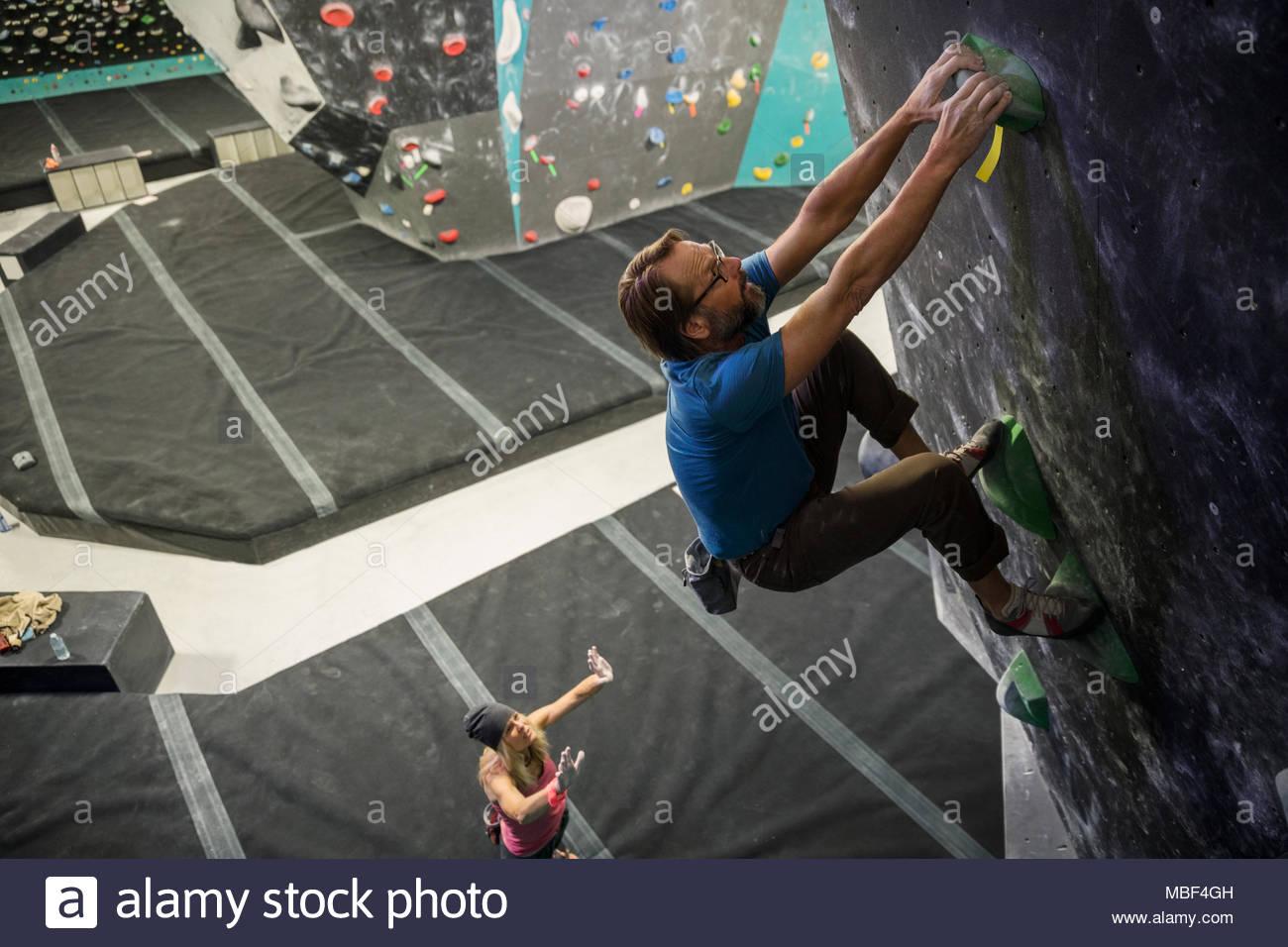 Woman spotting, guiding mature male rock climber climbing wall at climbing gym - Stock Image