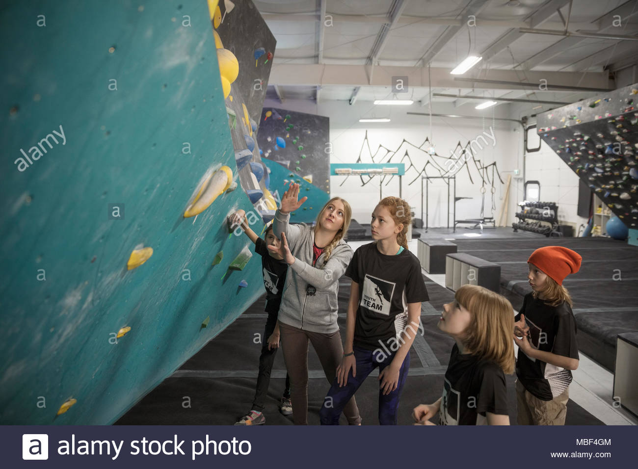 Female instructor teaching girl rock climbing students at climbing wall in climbing gym - Stock Image