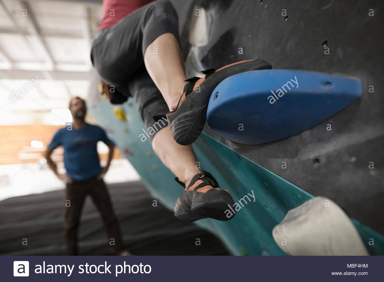 Close up rock climber stepping, climbing wall at climbing gym - Stock Image