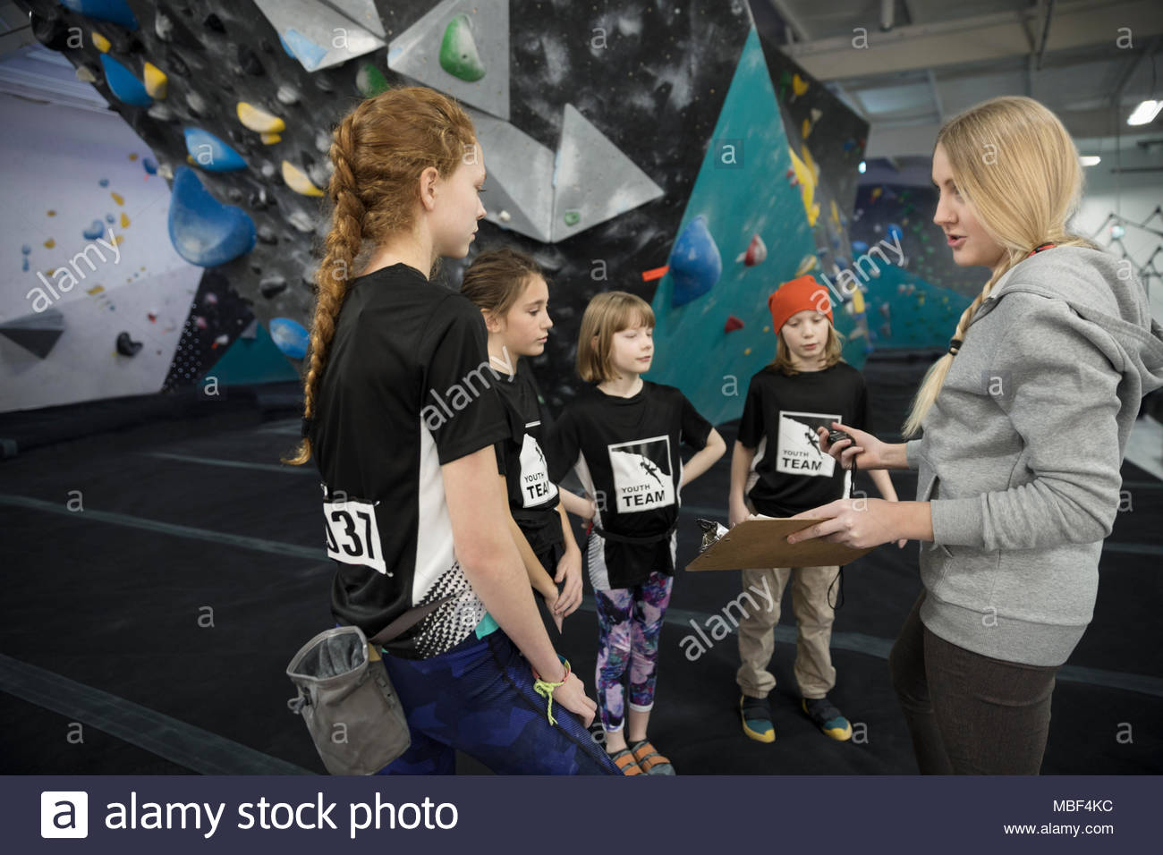 Female instructor with clipboard giving lesson to rock climbing students at climbing wall in climbing gym - Stock Image
