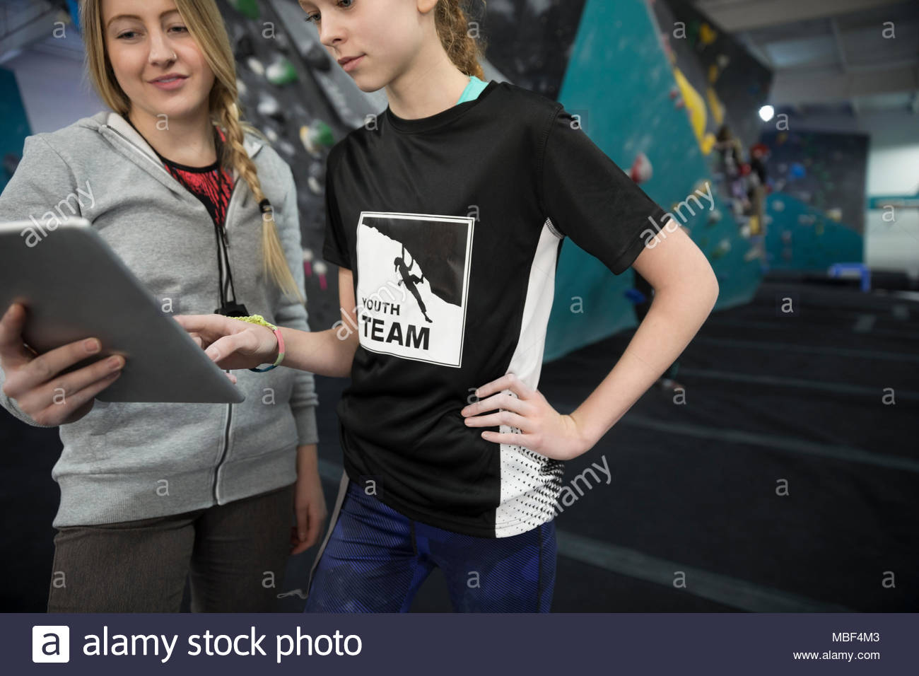 Female instructor and girl rock climbing student using digital tablet at climbing wall in climbing gym - Stock Image