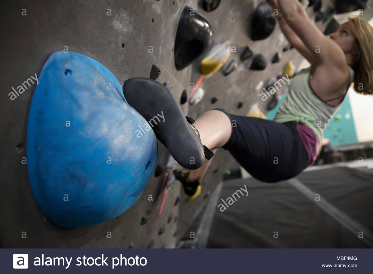 Determined, tough female rock climber climbing wall in climbing gym - Stock Image
