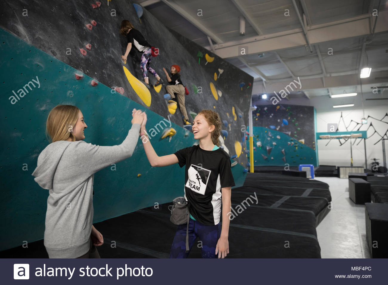 Female instructor and girl rock climbing student high-fiving at climbing wall in climbing gym - Stock Image