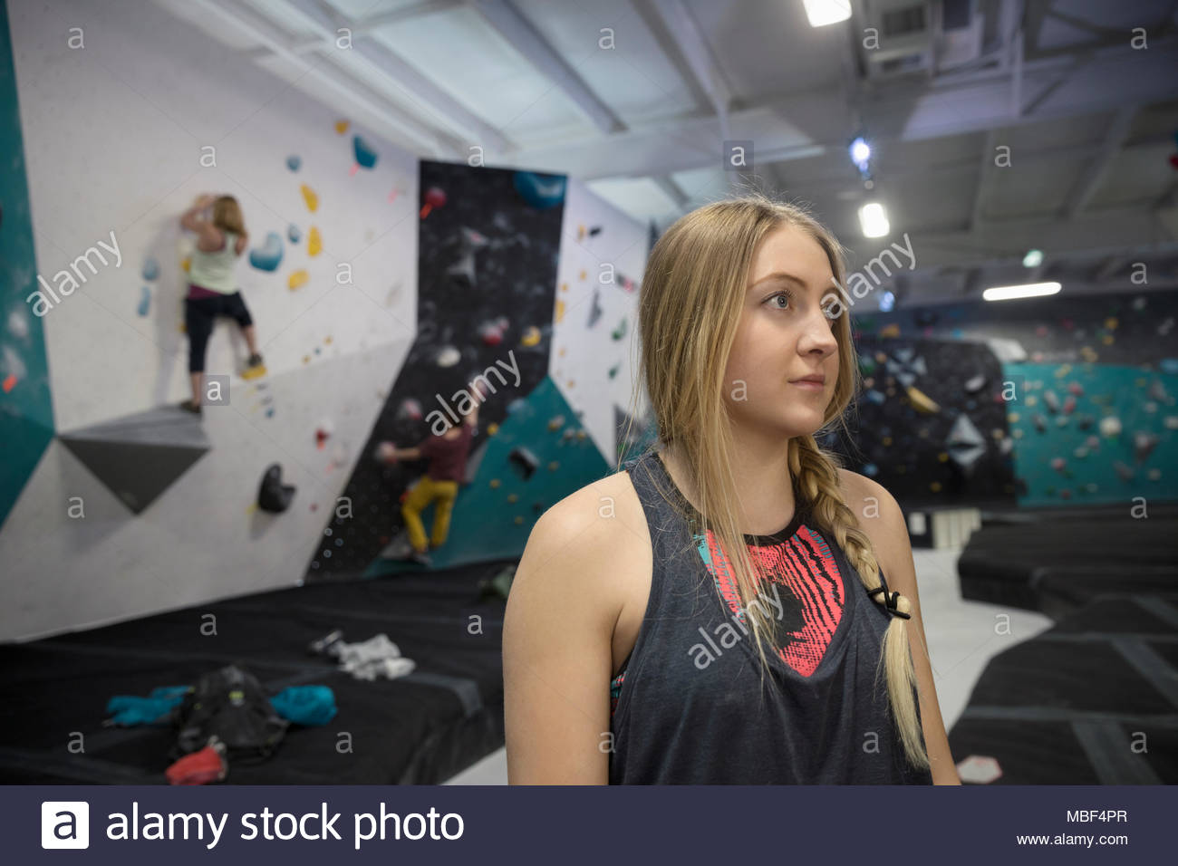 Determined, focused female rock climber at climbing gym - Stock Image