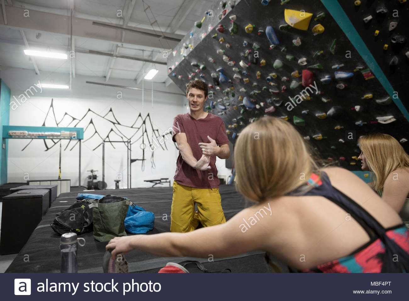 Rock climbers stretching hands and legs at climbing gym - Stock Image
