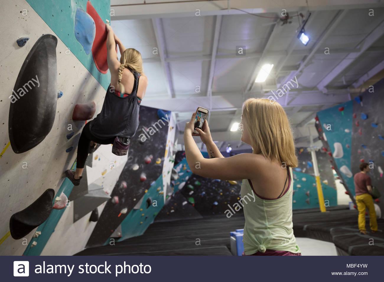 Female rock climber with camera phone videoing partner climbing wall at climbing gym - Stock Image