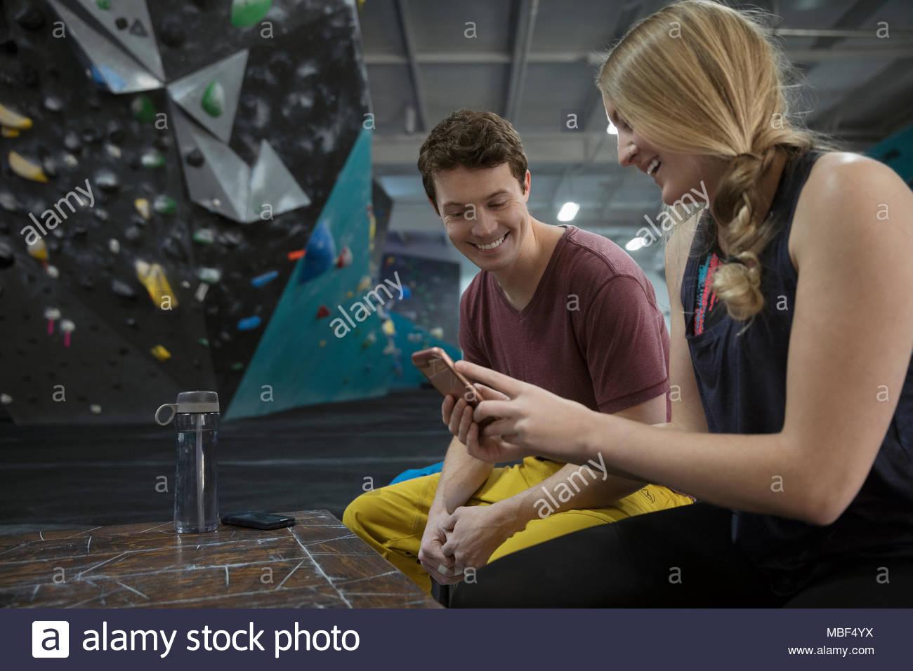 Rock climbers using smart phone at climbing gym Stock Photo