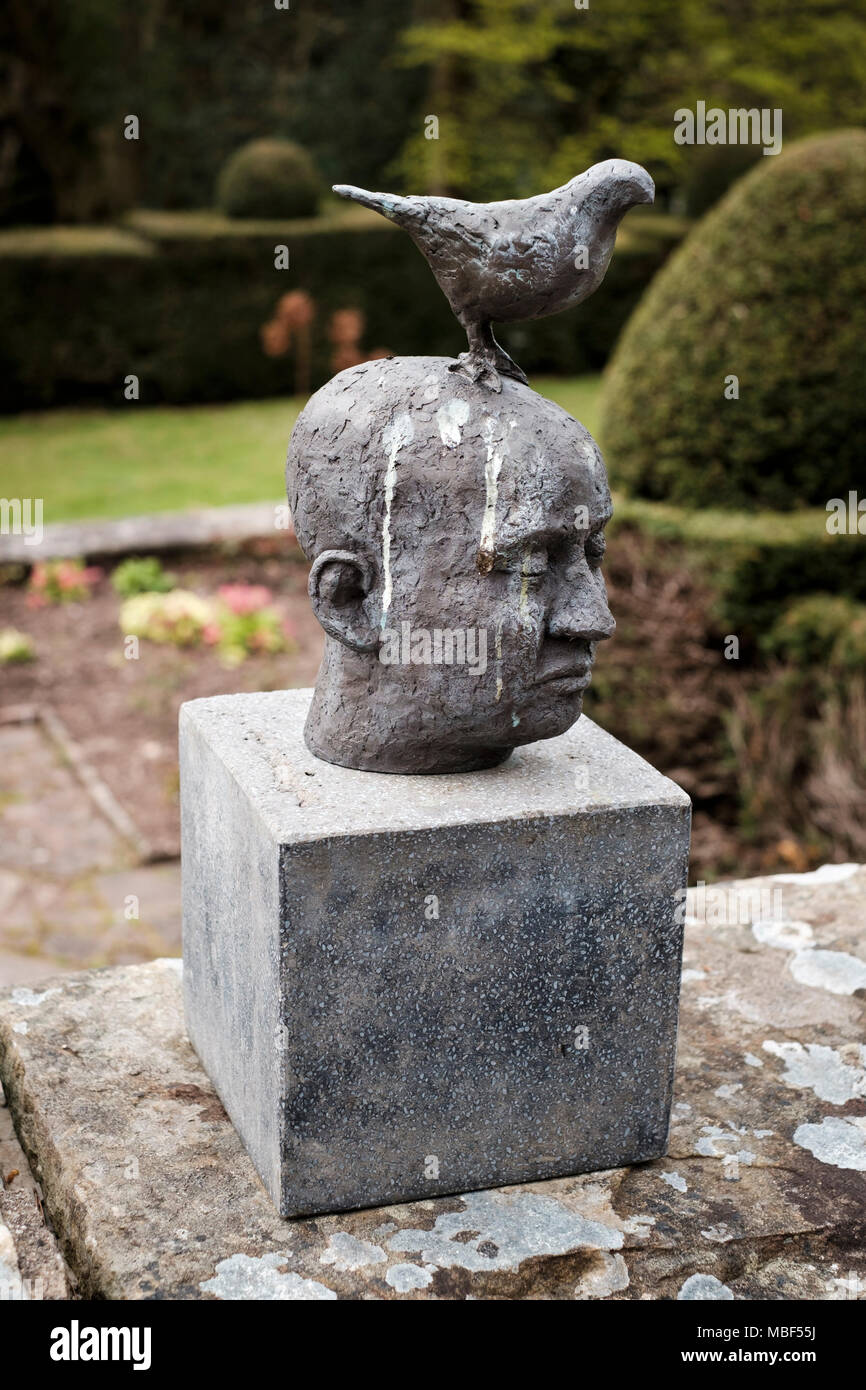 Sculpture of head with a bird perching and bird droppings Wyndcliffe Court Sculpture Gardens Monmouthshire - Stock Image