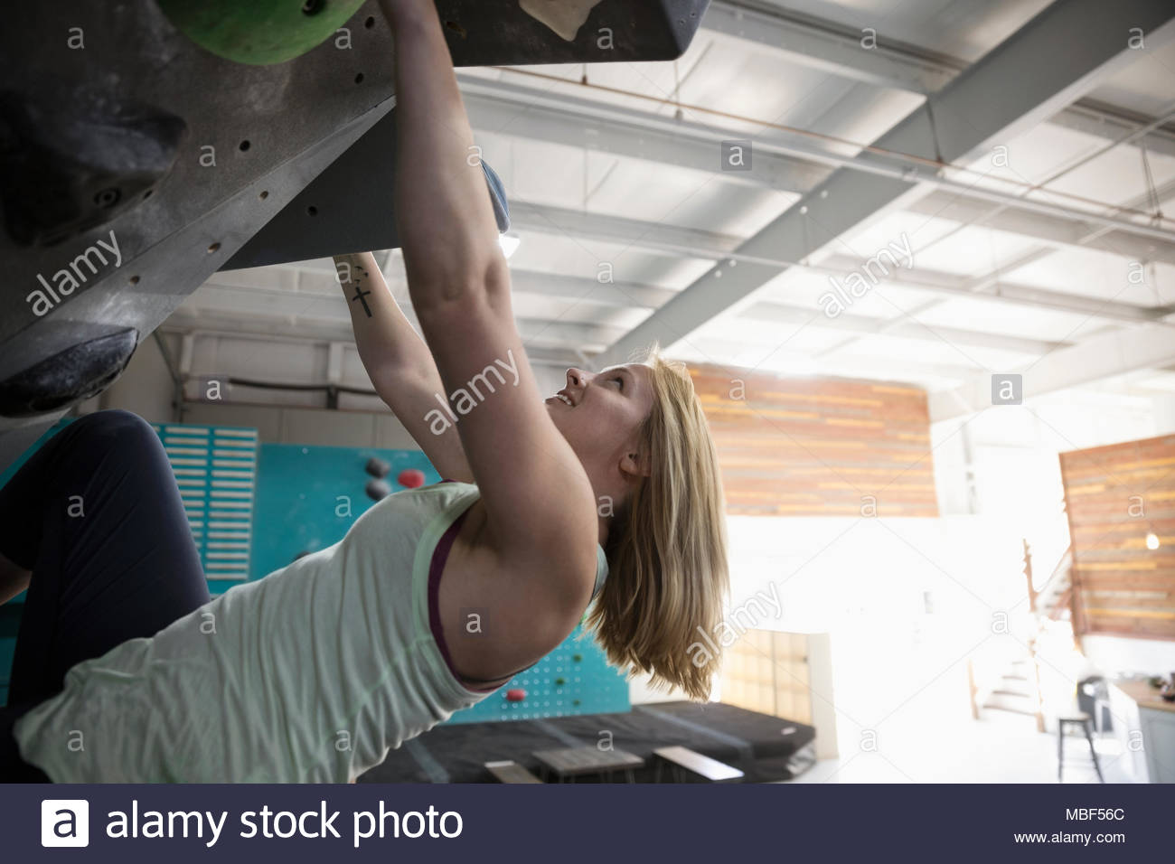 Determined female rock climber climbing wall at climbing gym - Stock Image