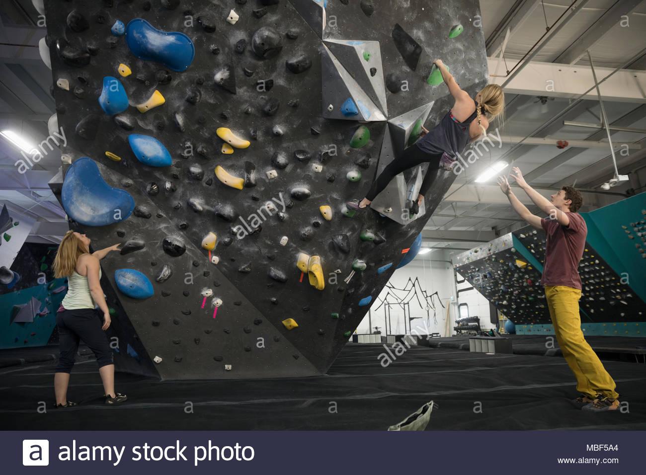 Rock climber spotting partner climbing wall at climbing gym - Stock Image