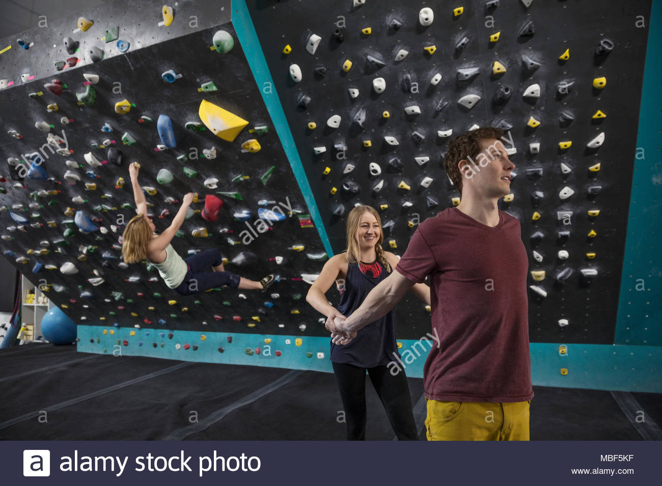 Rock climbers helping each other stretch, preparing at climbing gym - Stock Image