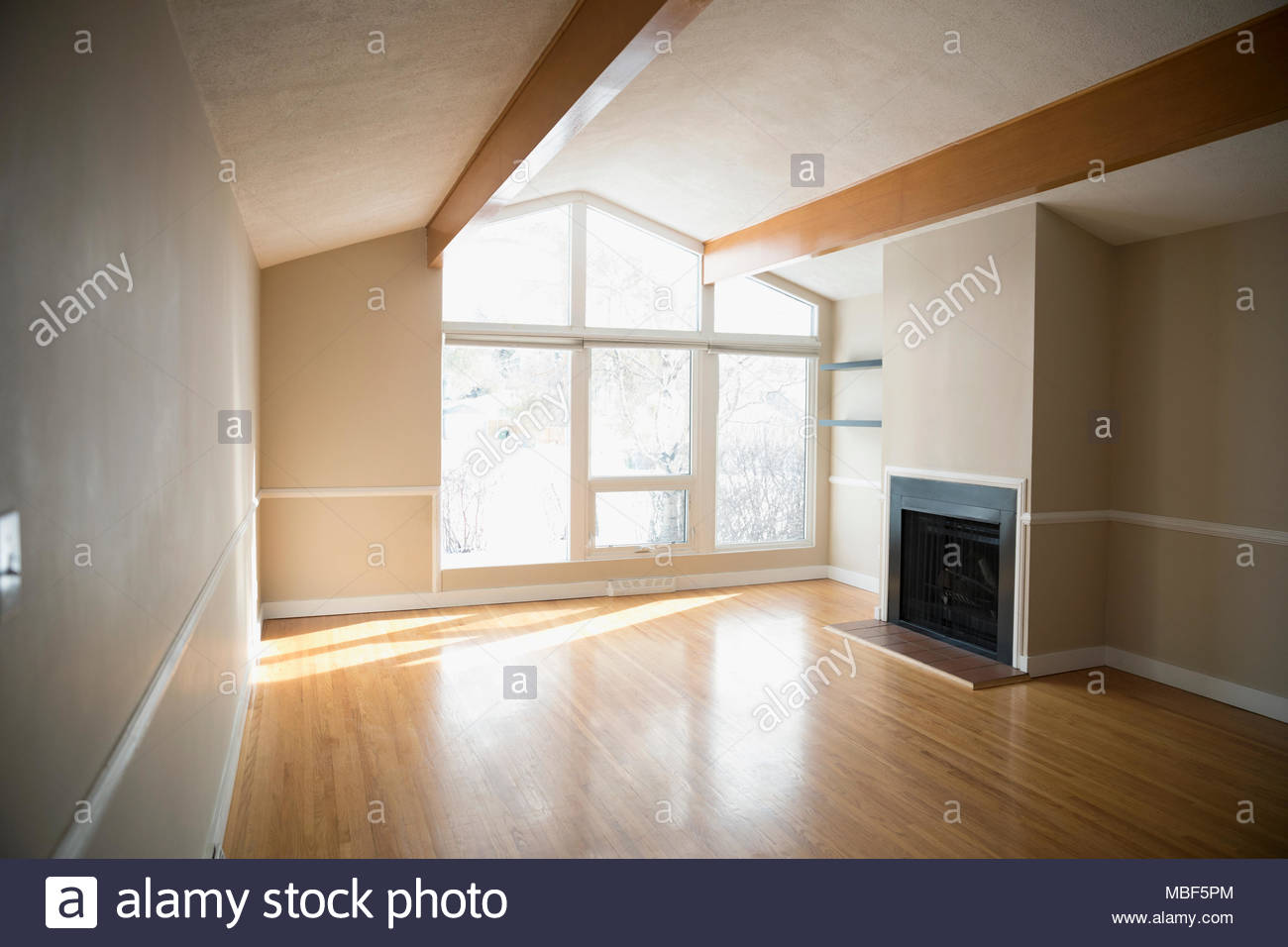 Sunny empty living room with hardwood floors and fireplace Stock ...