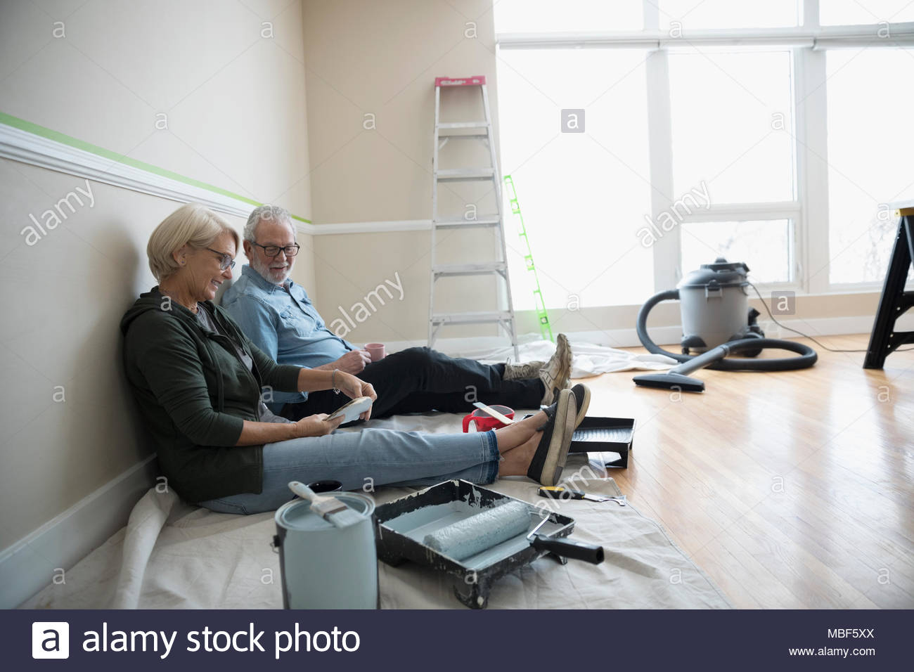 Senior couple preparing to paint in living room, looking at paint swatches, DIY - Stock Image