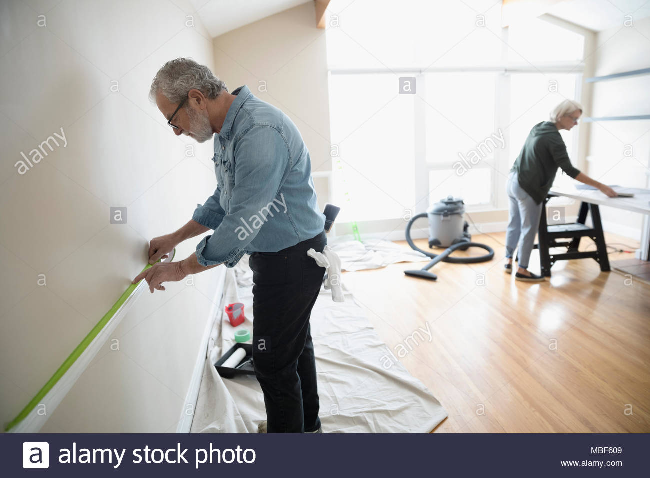 Senior man taping, preparing to paint chair rail in living room, DIY - Stock Image