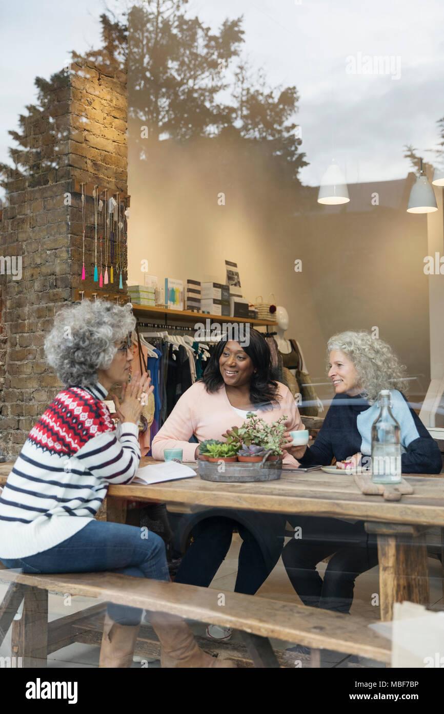 Women friends drinking tea in cafe shop window Stock Photo
