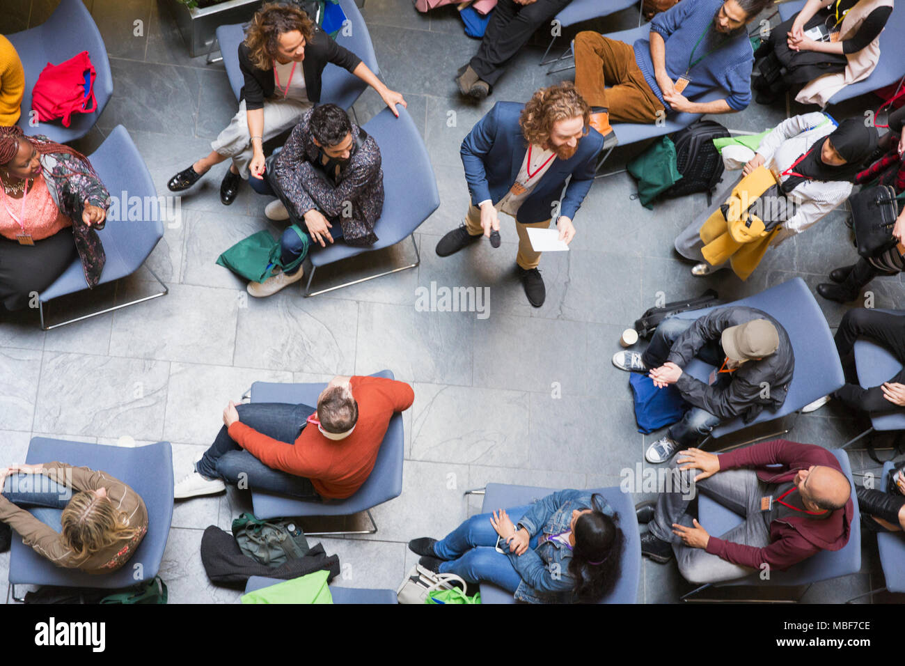 Overhead view conference audience listening to speaker with microphone - Stock Image