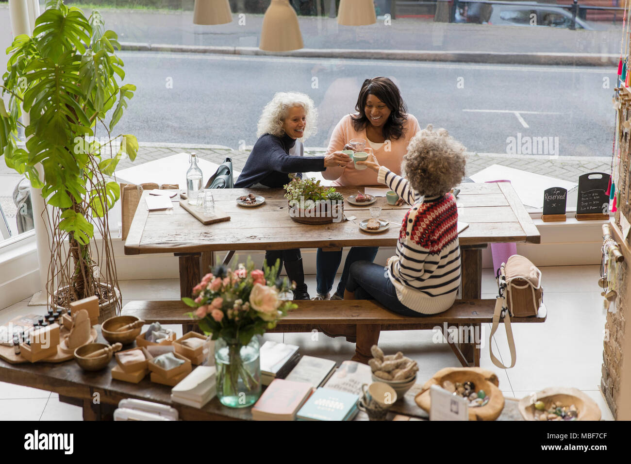 Women friends toasting teacups at cafe shop - Stock Image