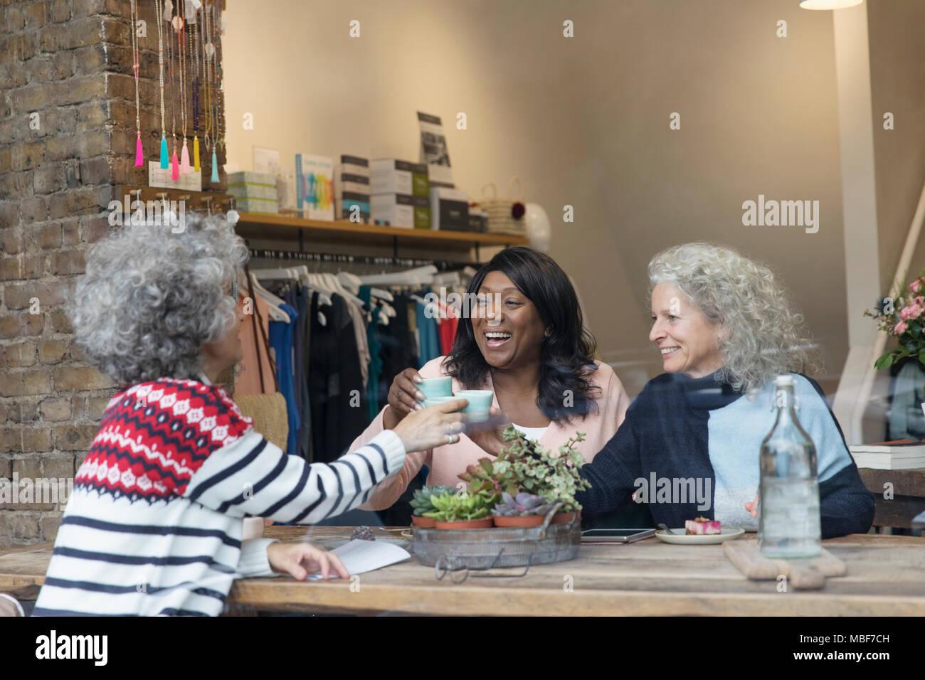 Women friends drinking tea in shop window Stock Photo