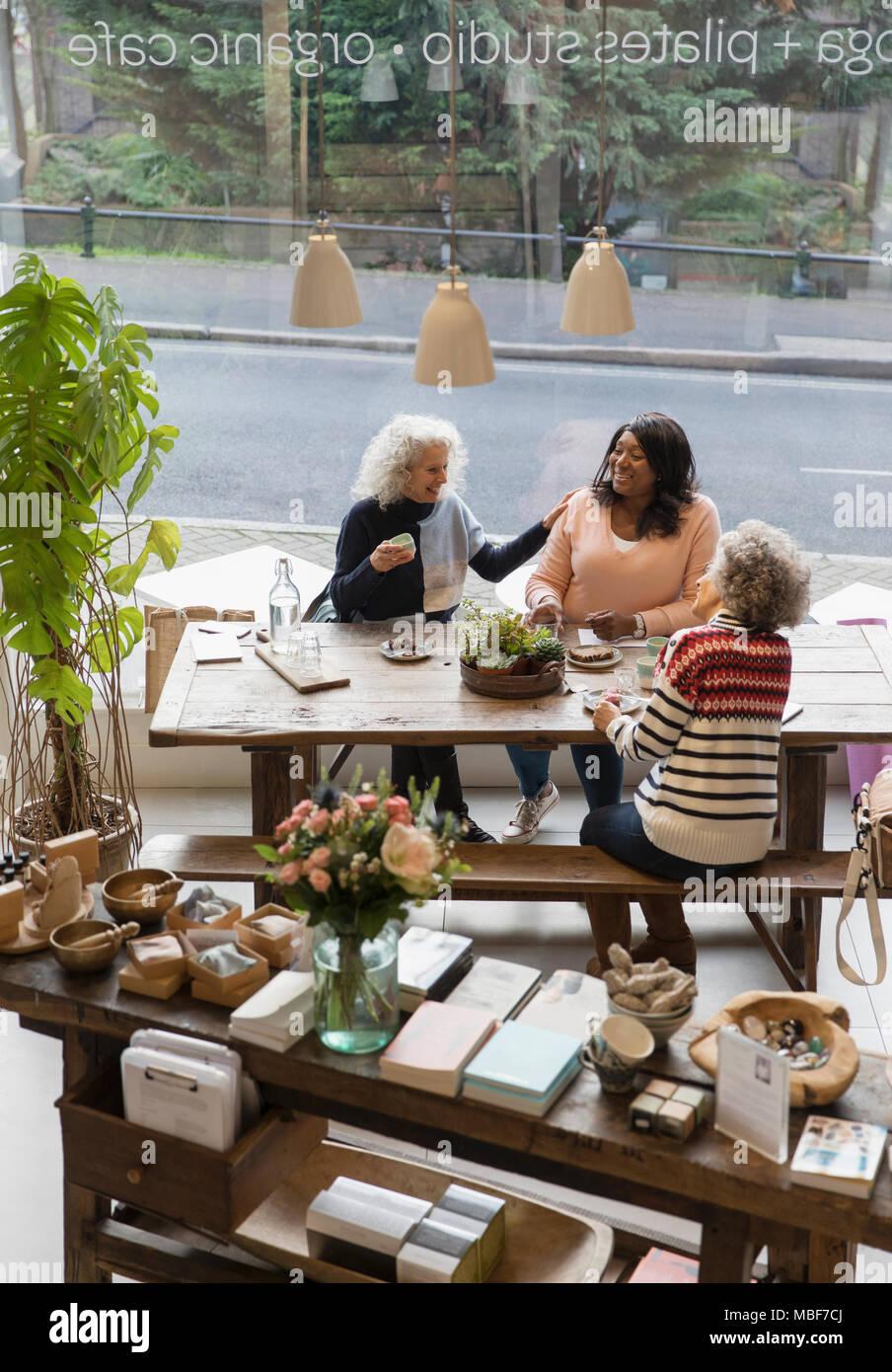 Women friends talking, drinking tea in shop Stock Photo