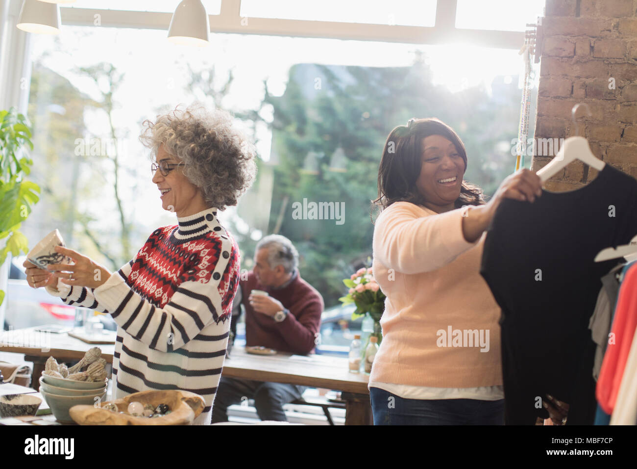 Women shopping in clothing store - Stock Image
