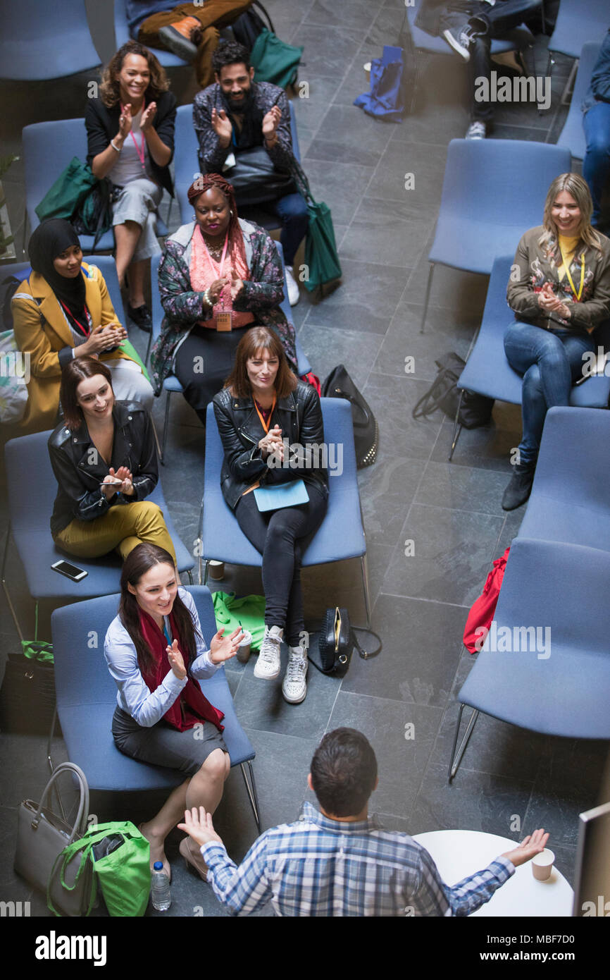 Conference audience clapping for male speaker - Stock Image